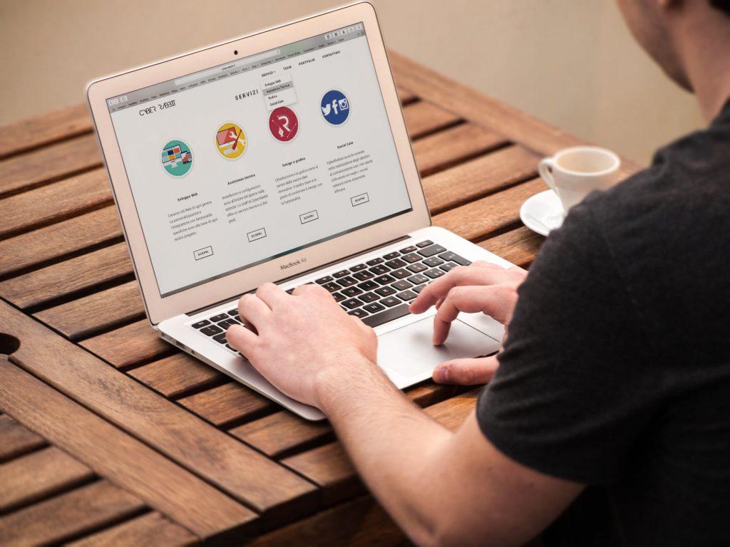 man at computer looking at social media sites